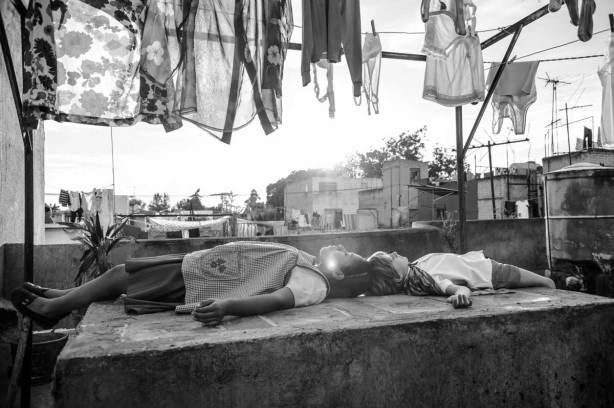 An still image from the film Roma showing a woman and boy lying down under a washing line and looking up at the sky